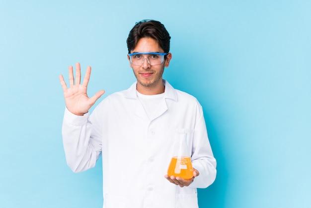 Junger cientific kaukasischer mann lokalisierte lächelnde nette darstellende nr. fünf mit den fingern.