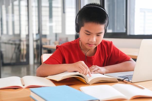Junger collage-student, der computer und mobiles gerät verwendet, um online zu studieren. bildung und online-lernen.