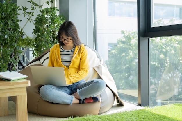 Junger collagenstudent, der den computer und tragbares gerät online studieren verwendet.
