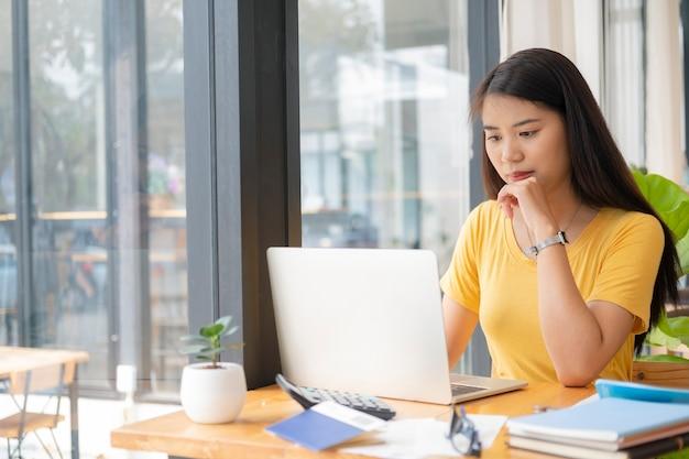 Junger collagestudent, der computer und mobiles gerät verwendet, das online studiert. bildung und online-lernen.