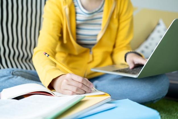 Junger collagestudent, der computer und mobiles gerät verwendet, das online studiert.