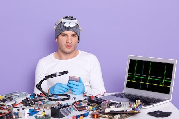 Junger computerspezialist, der kaputtes smartphone repariert, bereit ist, es zu zerlegen, am tisch voller werkzeuge sitzt, radiotrician, der elektronische ausrüstung im service-center testet. elektronisches ingenieurwesen