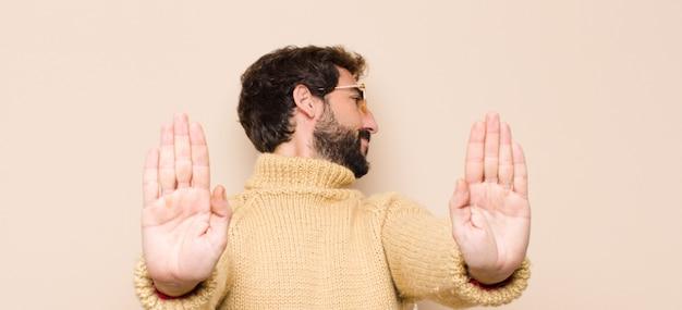 Junger cooler mann, der ernst, unglücklich, wütend und unzufrieden aussieht, den eintritt zu verbieten oder zu sagen, stoppen sie mit beiden offenen handflächen gegen flache wand