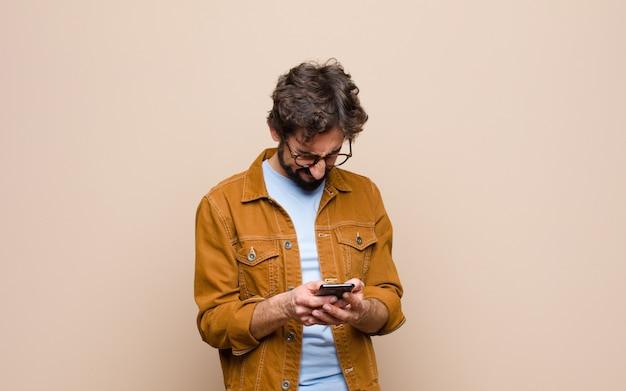 Junger cooler mann, der sein smartphone benutzt