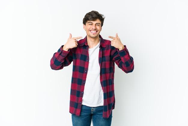 Junger cooler mann lächelt und zeigt mit den fingern auf den mund.