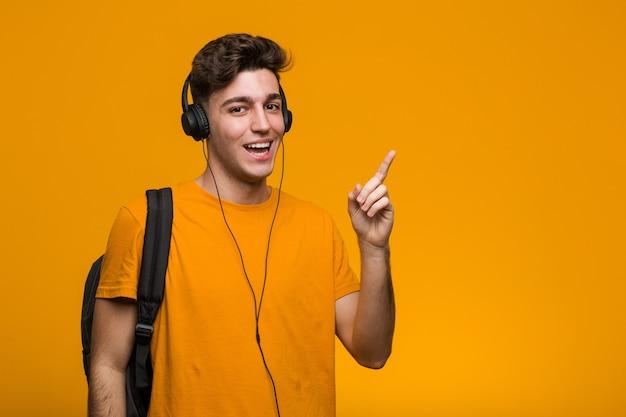 Junger cooler studentenmann, der musik mit kopfhörern hört, die mit dem finger auf sie zeigen, als ob die einladung näher kommt.