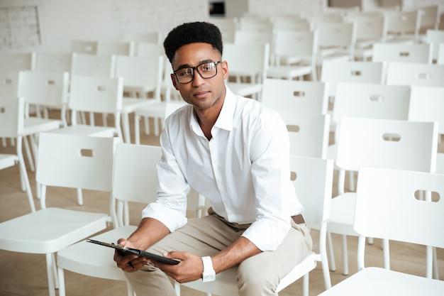 Junger denkender afrikanischer mann, der coworking sitzt