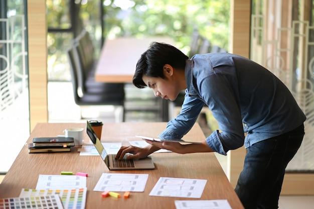 Junger designer, der in einem büro arbeitet er bückte sich, um den laptop zu benutzen, und hielt das tablet in der hand.