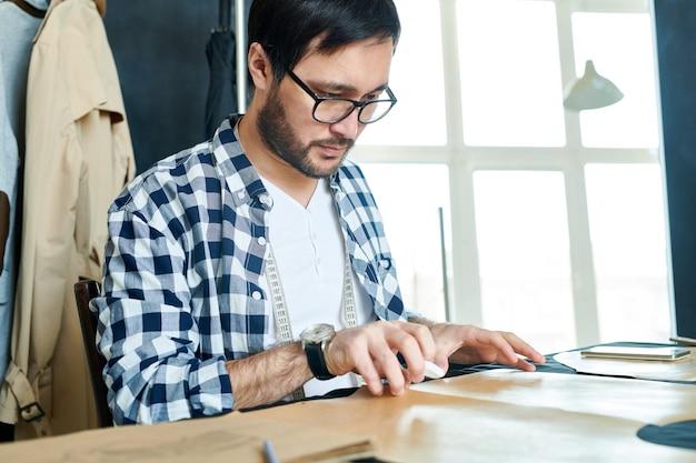 Junger designer, der mit schnittmustern arbeitet