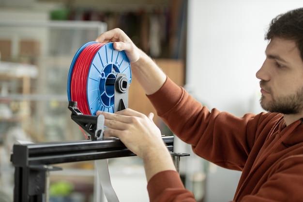 Junger designer, der spule mit rotem filament in 3d-drucker setzt, während er neue gegenstände bei der arbeit druckt