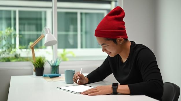 Junger designer, der stiftstiftzeichnungsskizzen auf grafiktablett in seinem studio verwendet.