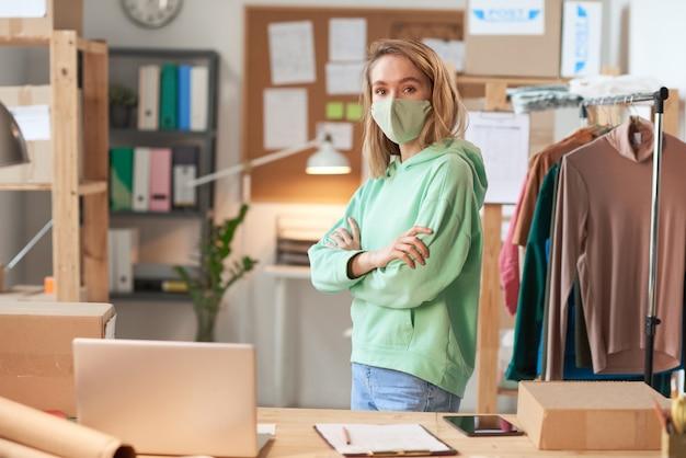 Junger designer in der schutzmaske, die vorne beim stehen mit verschränkten armen in werkstatt schaut