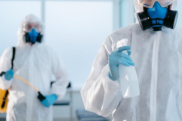 Junger desinfektor mit einer flasche antiseptikum im zimmer stehend