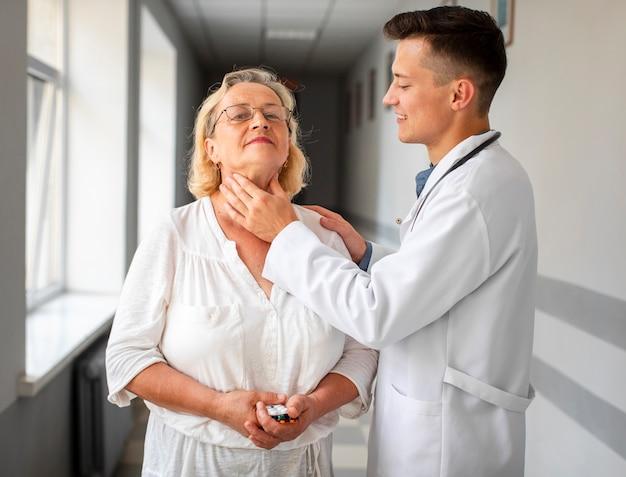 Junger doktor, der ältere frau konsultiert