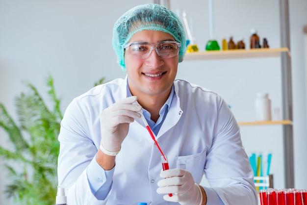 Junger doktor, der an blutprobe im laborkrankenhaus arbeitet