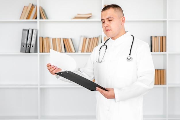 Junger doktor, der auf blättern von einem klemmbrett schaut