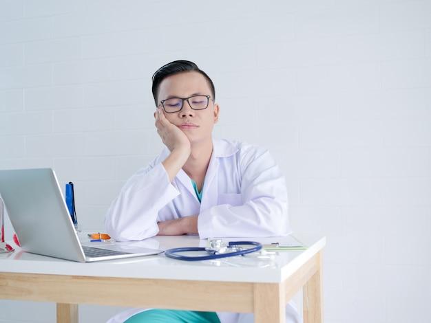 Junger doktor, der auf seiner hand im büro sich lehnt
