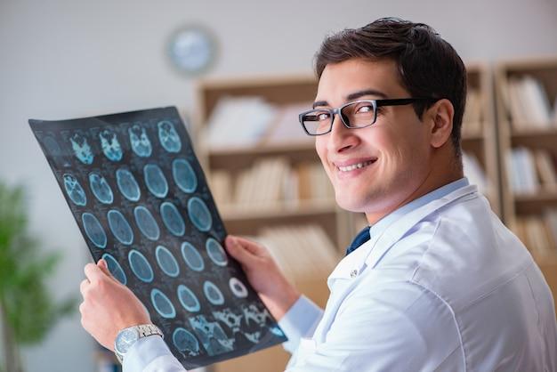 Junger doktor, der computertomographie-röntgenbild betrachtet