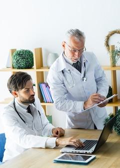 Junger doktor, der dem älteren kollegen daten zeigt