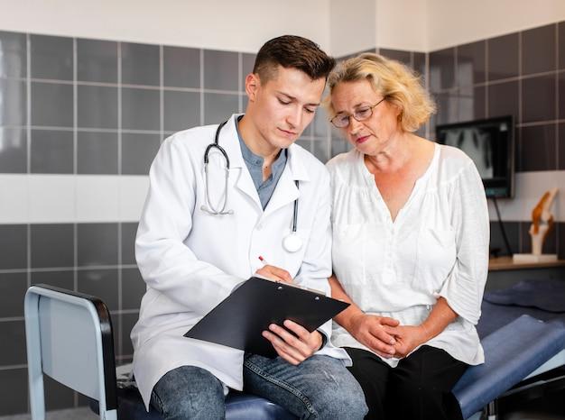 Junger doktor, der der älteren frau ergebnisse zeigt