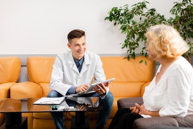 Junger doktor, der eine tablette hält und patienten betrachtet