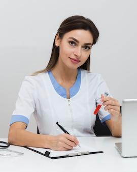 Junger doktor, der einen bericht schreibt und eine blutprobe hält