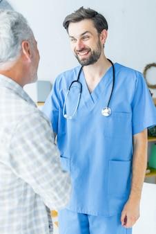Junger doktor, der hand des älteren patienten rüttelt
