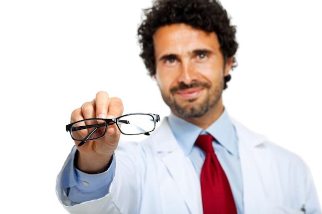 Junger doktor, der ihnen ein paar brillen gibt