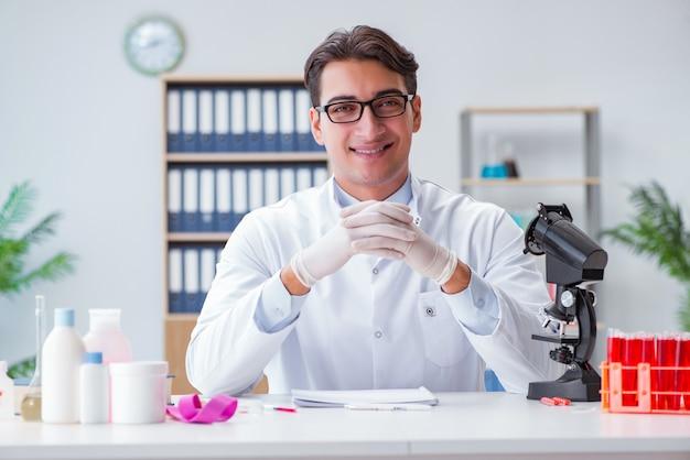 Junger doktor, der im labor mit mikroskop arbeitet