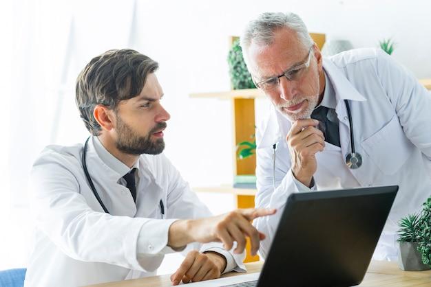 Junger doktor, der mit älterem kollegen sich berät