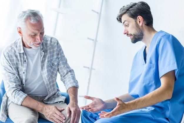 Junger doktor, der mit älterem patienten spricht