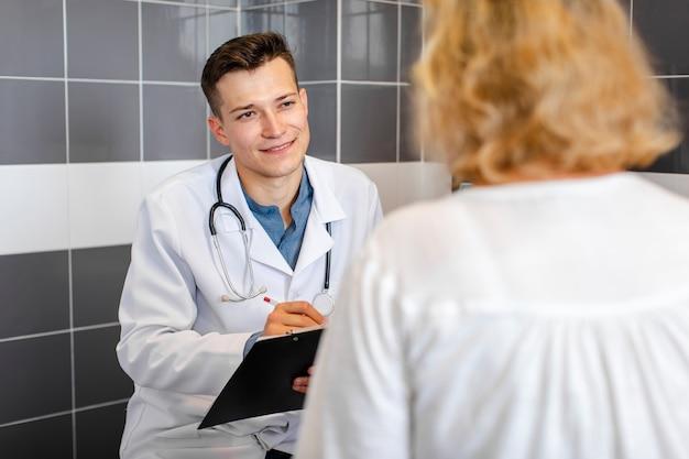 Junger doktor, der mit einem patienten im kabinett spricht