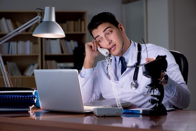 Junger doktor, der spät im büro arbeitet