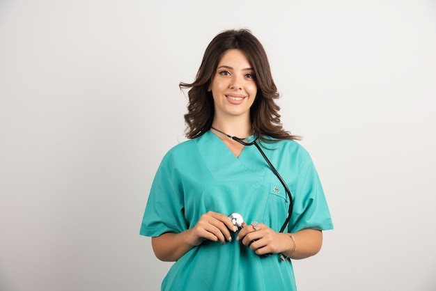 Junger doktor, der stethoskop auf weiß verwendet.