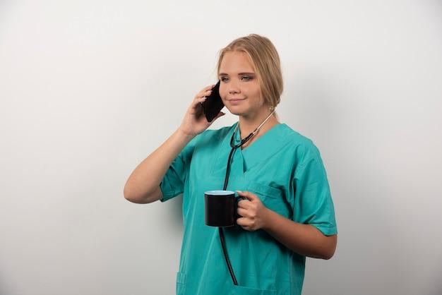 Junger doktor, der tee beim gespräch mit telefon hält.