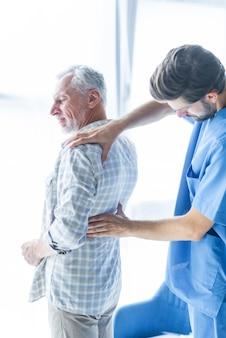 Junger doktor, der zurück schmerzt vom älteren mann überprüft