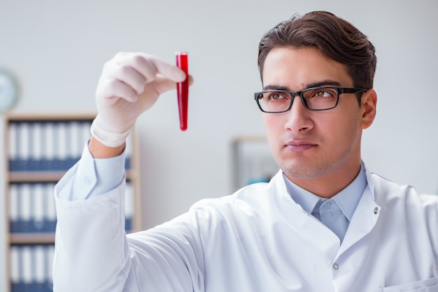 Junger doktor im labor mit rotem gefäß