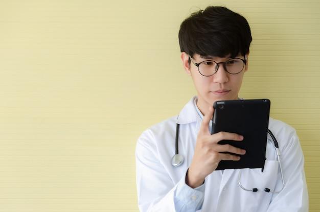 Junger doktor in der weißen uniform, die digitale tablette ernst betrachtet