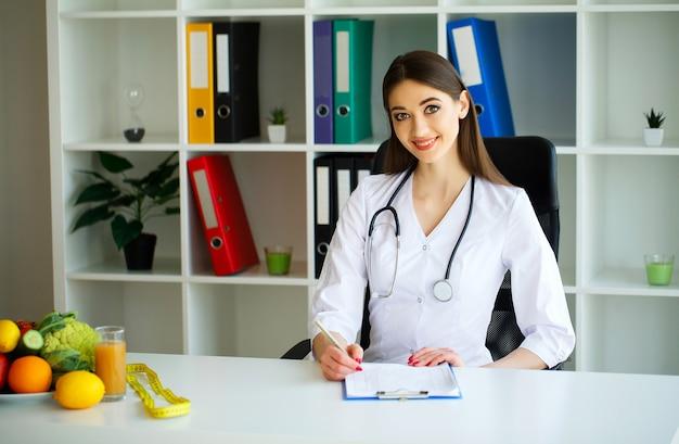 Junger doktor mit einem schönen lächeln im hellen büro.