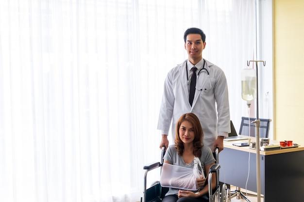 Junger doktor regte den weiblichen patienten auf dem gebrochenen arm und dem rollstuhlpatienten an.