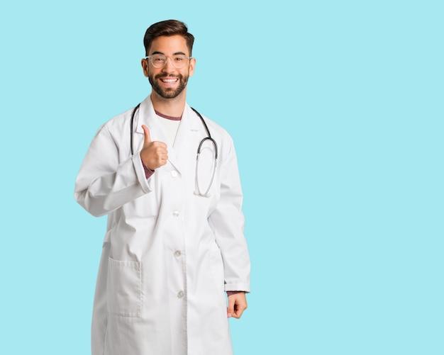 Junger doktormann, der daumen lächelt und anhebt