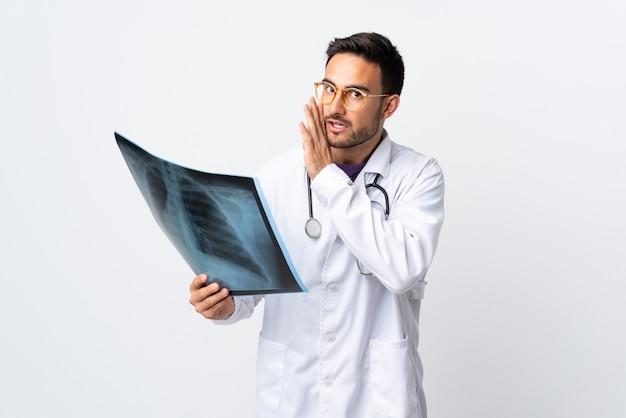 Junger doktormann, der eine radiographie lokalisiert auf weißem hintergrund hält, der etwas flüstert Premium Fotos