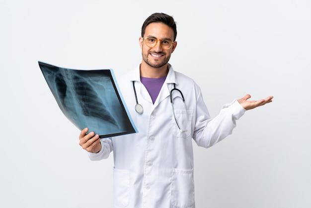 Junger doktormann, der eine radiographie lokalisiert hält, die auf weiß gehaltenem copyspace imaginär auf der handfläche lokalisiert ist
