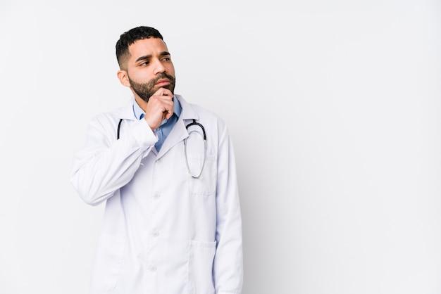 Junger doktormann, der mit zweifelhaftem und skeptischem ausdruck seitwärts schaut