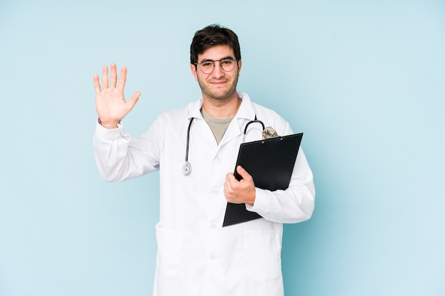 Junger doktormann lokalisiert auf blauem hintergrund lächelnd fröhlich zeigt nummer fünf mit den fingern.