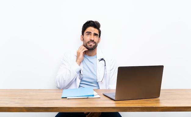 Junger doktormann mit seinem laptop über lokalisierter wand eine idee denkend