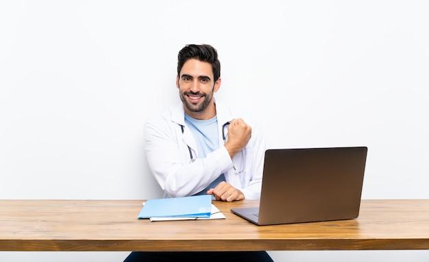 Junger doktormann mit seinem laptop über lokalisierter wand einen sieg feiernd