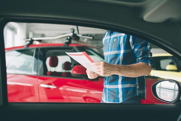 Junger dunkelhaariger bärtiger mann, der das auto im autohaus untersucht und seine wahl trifft.