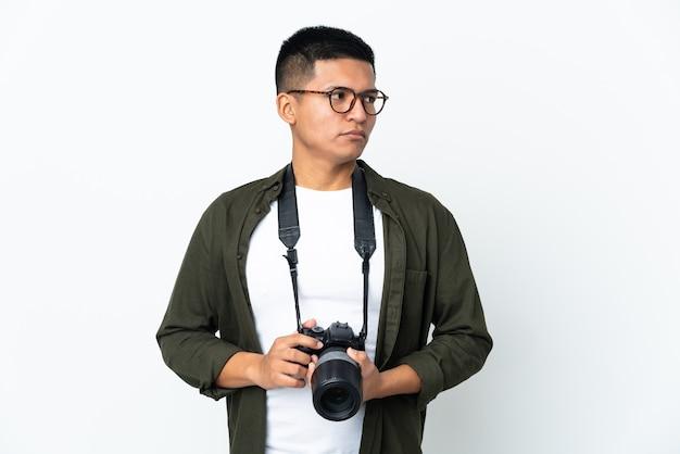 Junger ecuadorianischer fotograf lokalisiert auf weißer wand, die zur seite schaut