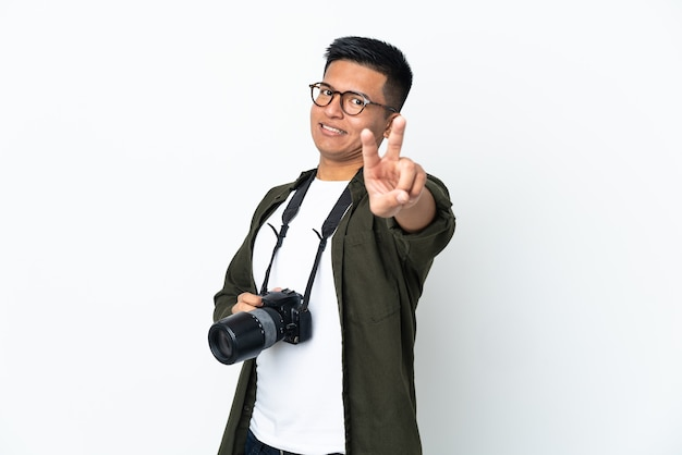 Junger ecuadorianischer fotograf lokalisiert auf weißer wand lächelnd und siegeszeichen zeigend